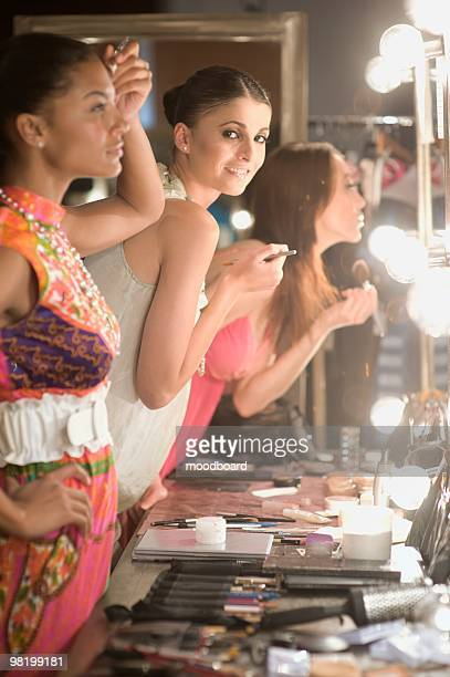 Three women apply makeup in dressing room mirror