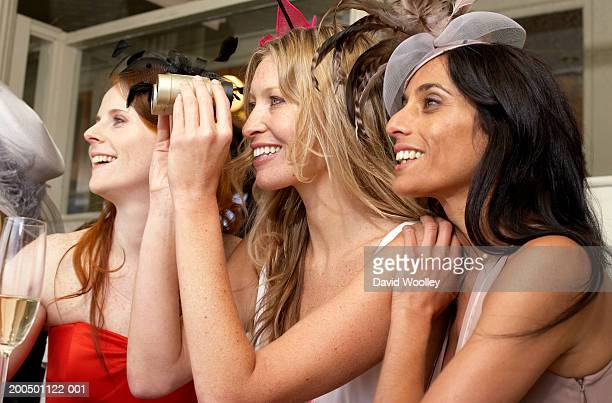 Three women at the races, smiling, side view