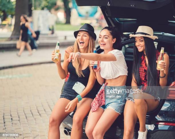Drei Frauen in den Kofferraum eines Autos, Bier zu trinken