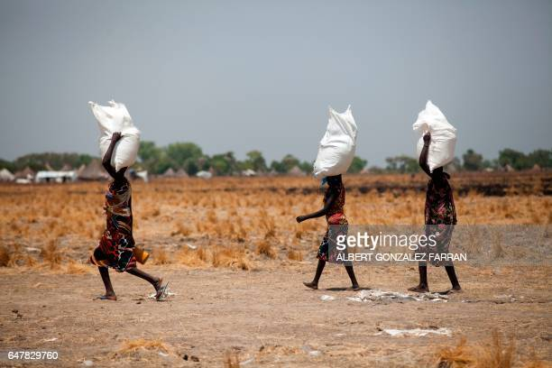 Three women carry a sack of food distributed on March 4 in Ganyiel Panyijiar county in South Sudan South Sudan was declared the site of the world's...