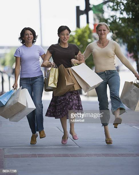 Three women carrying shopping bags