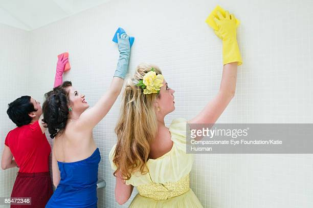 Three women cleaning bathroom