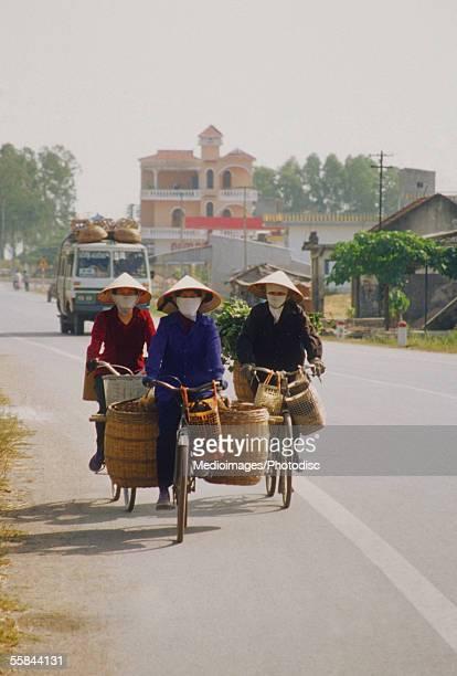 Three women cycling on a street, Vietnam