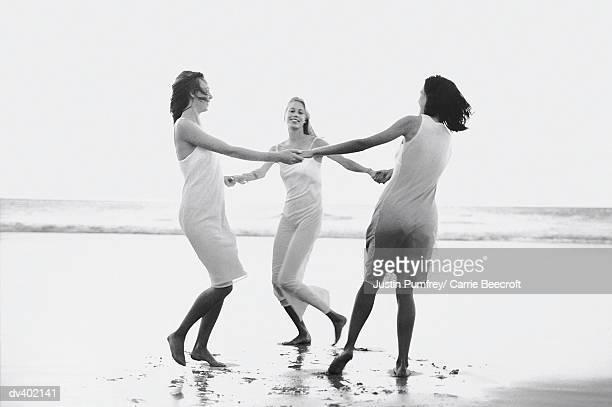 Three women dancing in circle on beach