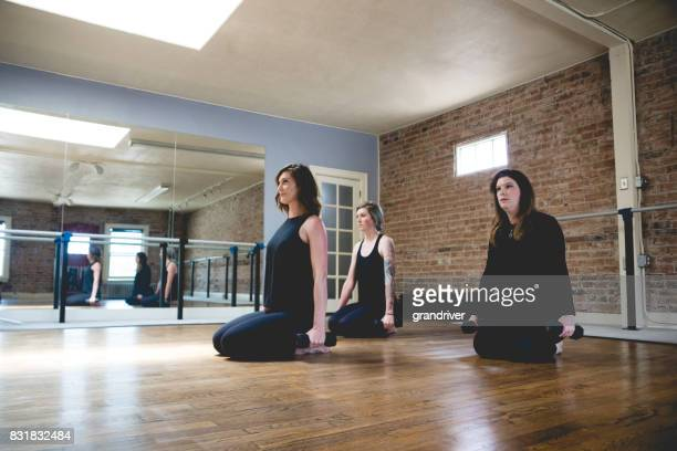 Three Women Doing Barre Floor Exercises with Dumbbels