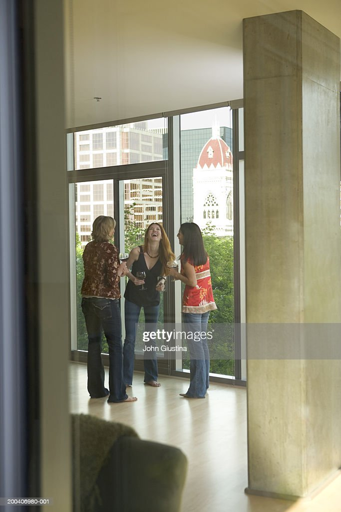 Three women drinking wine in loft apartment, laughing