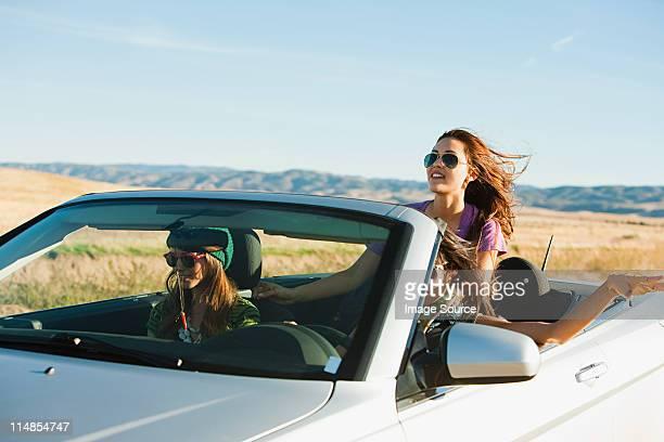 Three women driving in convertible car