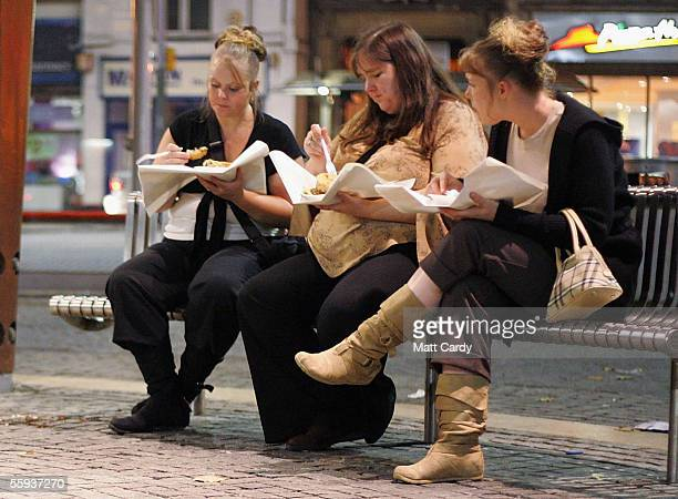 Three women eat takeaway food after a nightout in Bristol City Centre on October 15 2005 in Bristol England Pubs and clubs are preparing for the new...