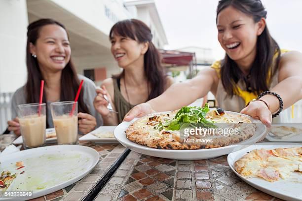 Three women enjoying a meal.