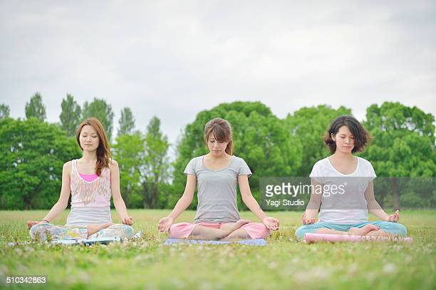 Three women enjoying yoga in park