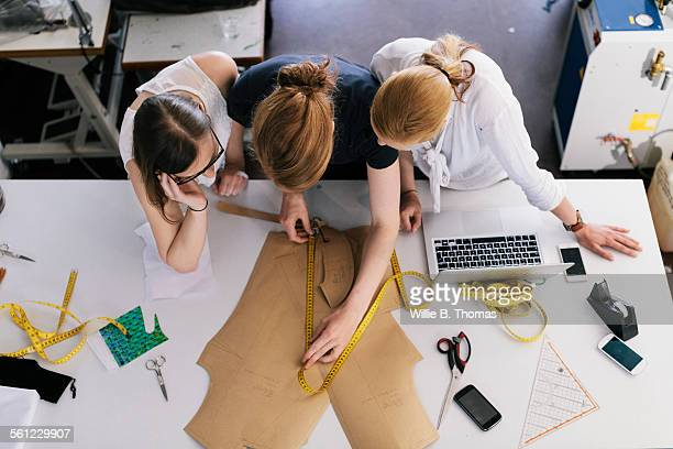 Three women fashion designers working with sewing