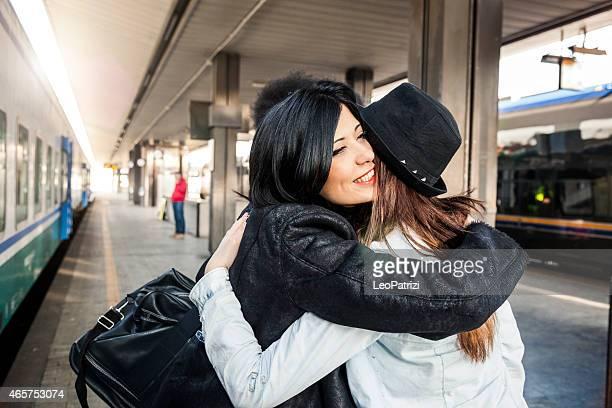 Three women friends greet at the train station