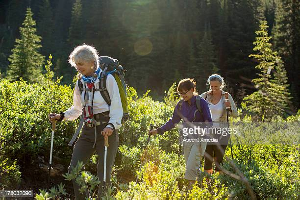 Three women hike through mountain meadow