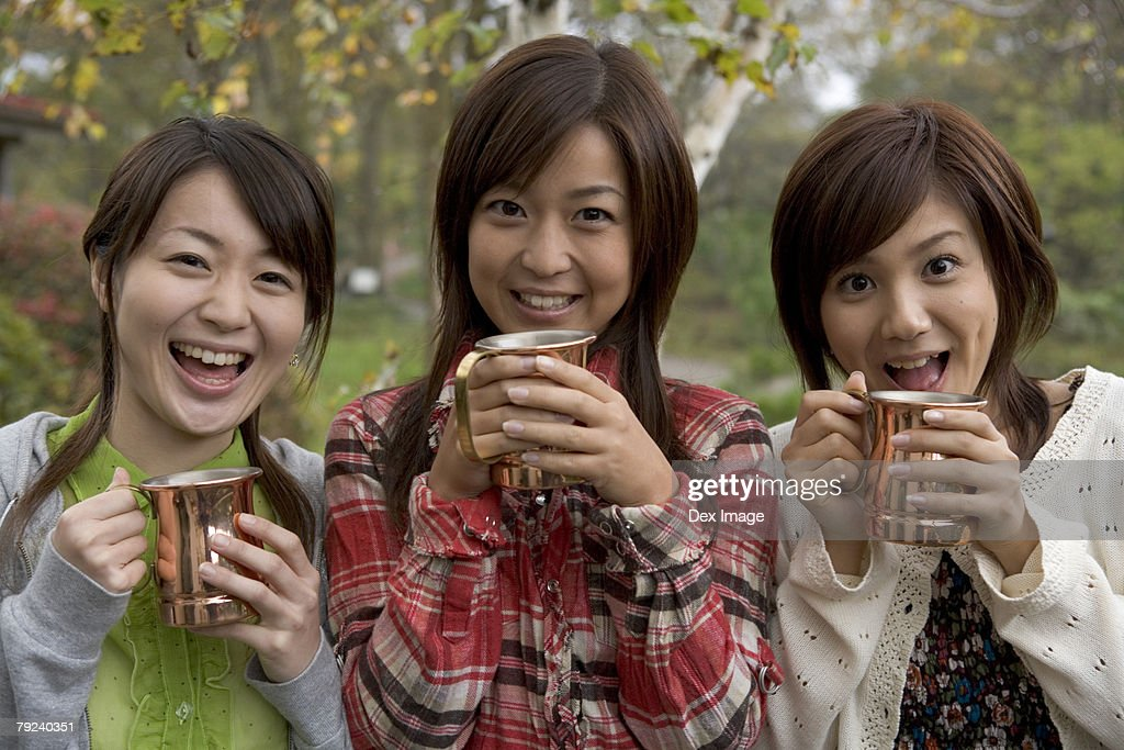 Three women holding cups : Stock Photo