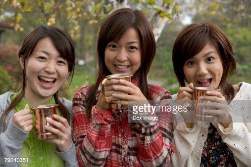 Three women holding cups : Stock Photo