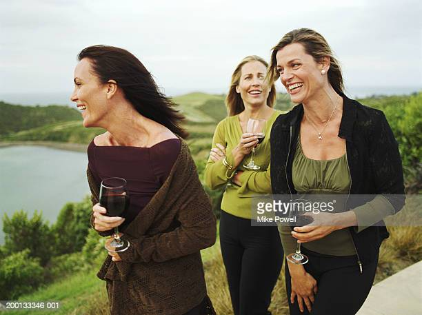 Three women holding glasses of wine, outdoors