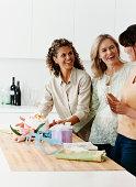 Three Women in a Kitchen Preparing a Birthday Cake and Birthday Gifts