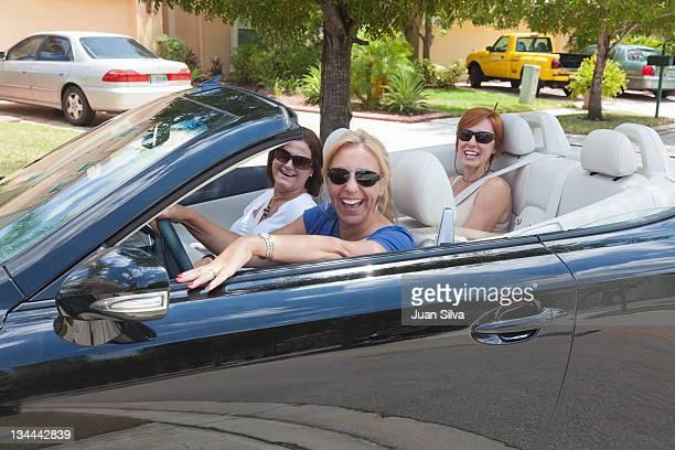 Three women in convertible car, smiling, portrait