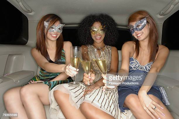Three women in limousine toasting champagne flutes wearing masks