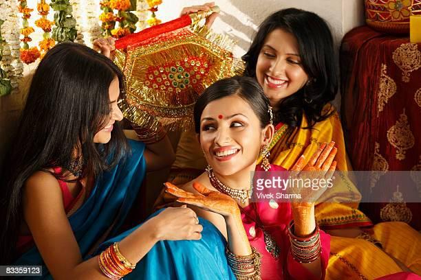 three women in saris, one showing her henna hands