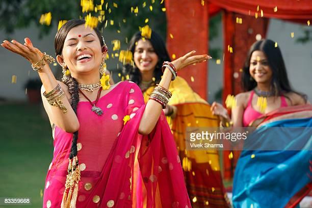 three women in saris, throwing petals