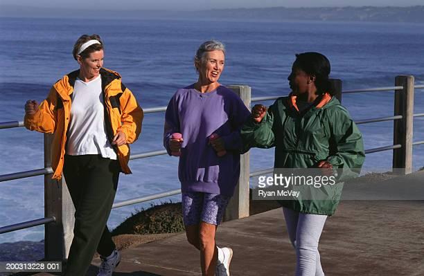 Three women jogging along pier