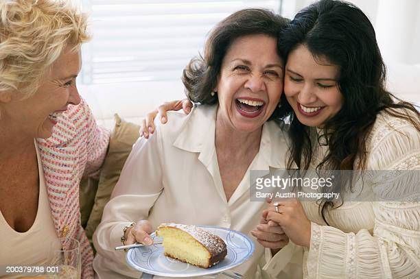 Three women laughing, one holding peice of cake