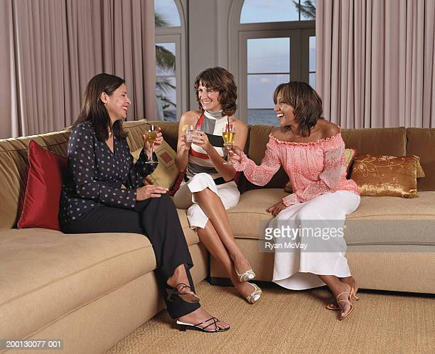 Three women laughing, raising toast on sofa