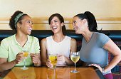 Three women laughing with cocktails indoors