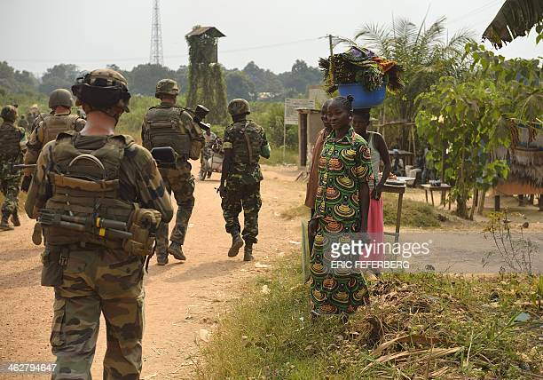 Three women look at French troup of the Sangaris operation and Burundian soldiers of the Misca patrolling on January 15 2014 in a street of Bangui...