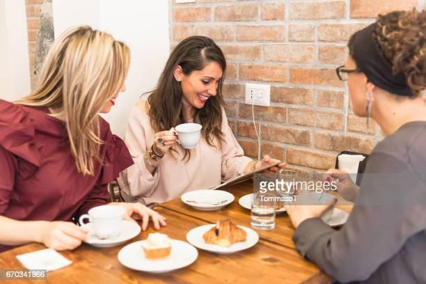three women looking at digital tabet having breakfast