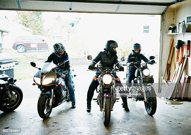 Three women on motorcycles backing out of garage