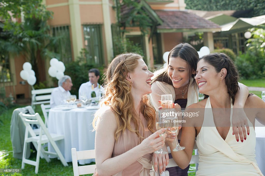 Three women outdoors at a party with champagne smiling for Ladeblok wit 3 lades