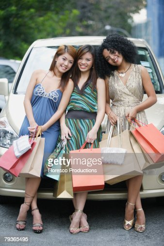 Three women outdoors with shopping bags leaning on car for Ladeblok wit 3 lades