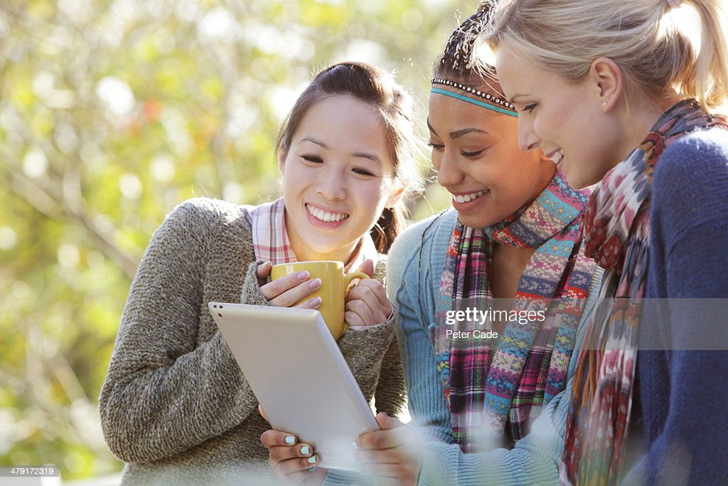 Three women outside looking at tablet : Stock Photo