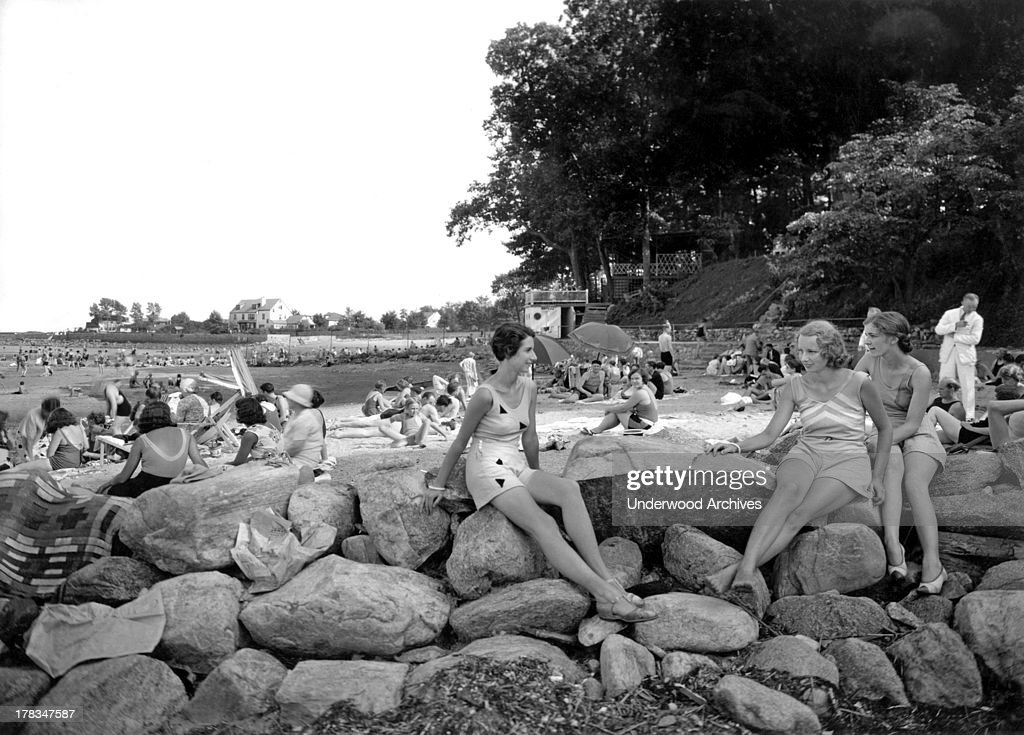 Three women perch on the rocks while enjoying an afternoon at the Shorewood Beach Club Stamford Connecticut c 1930