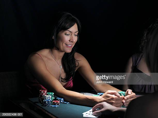 Three women playing poker, one smiling whilst gathering chips