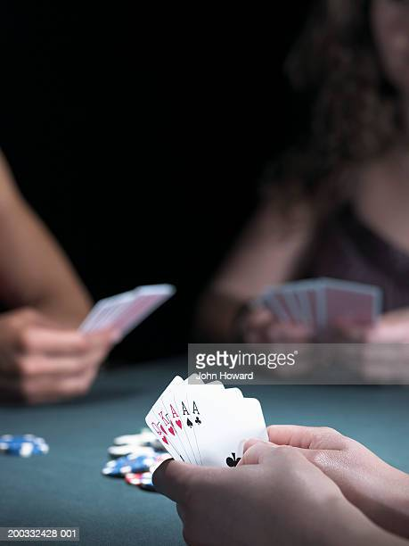 Three women playing poker, viewing hands, close-up