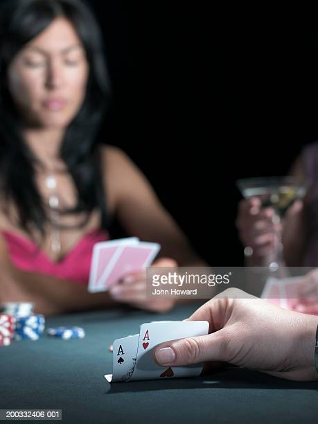 Three women playing poker, woman bending cards to reveal pair of aces