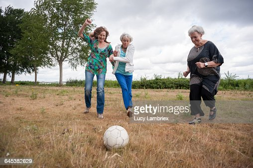 Three women playing soccer outdoors : Stockfoto