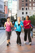 Group Of Women Power Walking On Urban Street Talking To Each Other Smiling