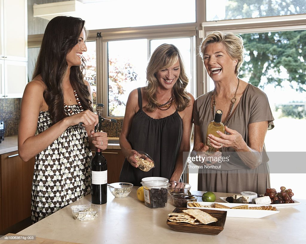 Three women preparing hors d'oeuvres in kitchen, smiling : Stock Photo