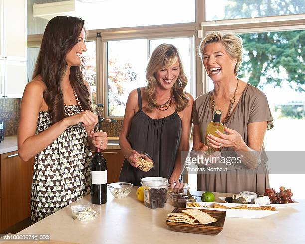 Three women preparing hors d'oeuvres in kitchen, smiling