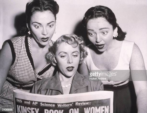 Three women react with shock as they read a newspaper review about the Kinsey Report on female sexual behavior 1950s