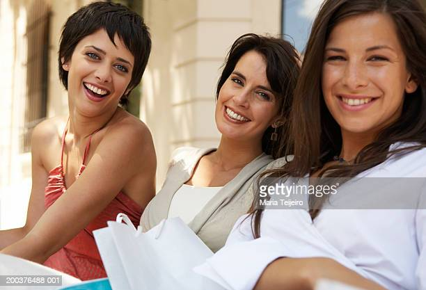 Three women relaxing outdoors, smiling, close-up, portrait