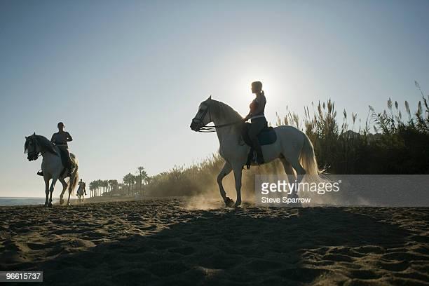 Three women riding horses on beach