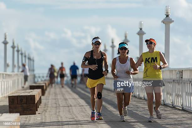 Three women run at the seafront in Fortaleza northeastern Ceara State of Brazil on April 17 2013 AFP PHOTO/Yasuyoshi CHIBA