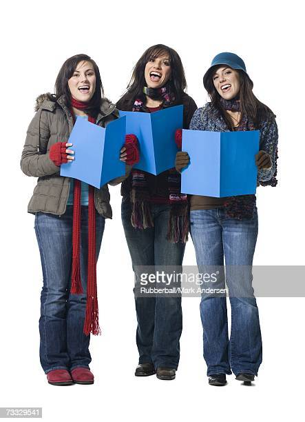 Three women singing with winter coats and sheet music