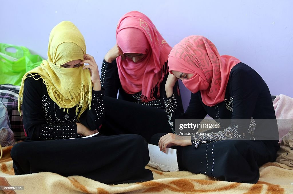 Three women sit on a blanket as Iraqi people in Fallujah town leave their home due to conflicts between Daesh and security forces in Anbar, Iraq on May 30, 2016. Some of the families who left their home are placed in a school in Karma Town, west of Anbar city.
