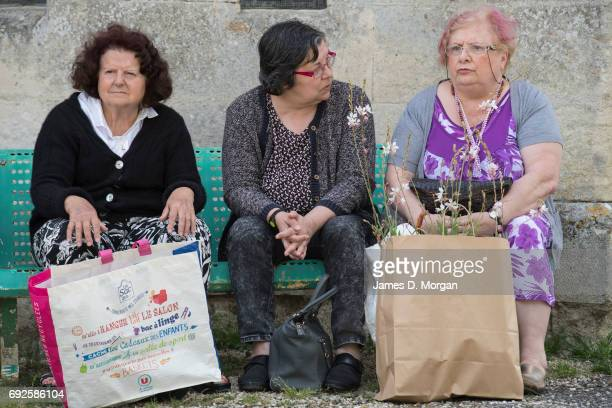 Three women sit with their purchases from a local fair on June 5 2017 in Saussignac France Monday is a public holiday in France celebrating 'Lundi de...